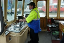 Paul Wilson standing at the wheel in the wheelhouse of his ferry
