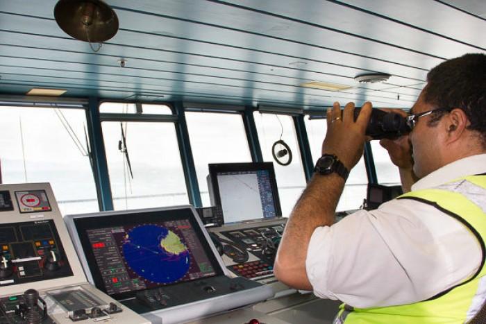 Man looking through binoculars out to sea