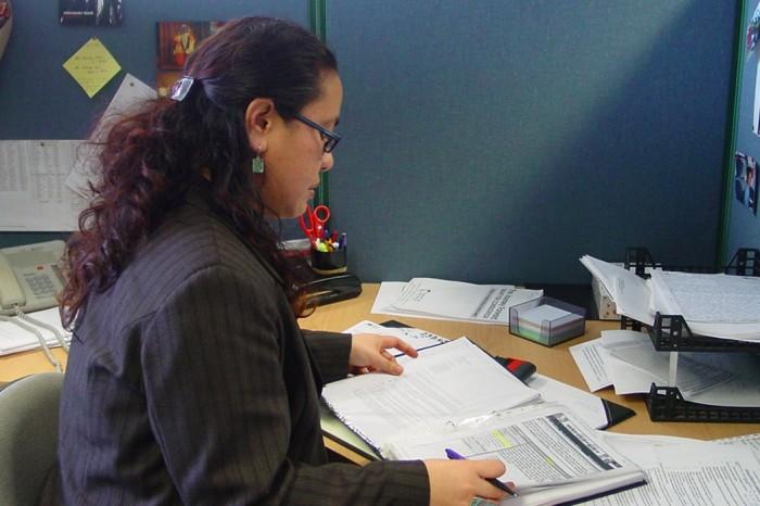 Janine Olasa Social Worker reviews files at her desk