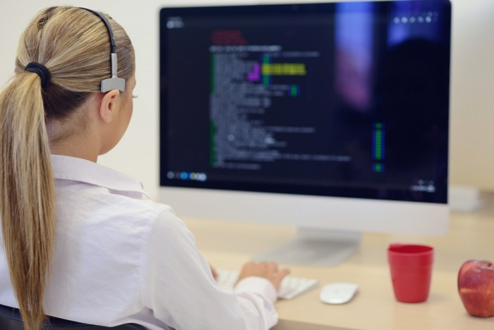 A woman wearing a headset sits at a computer looking at a screen full of computer code