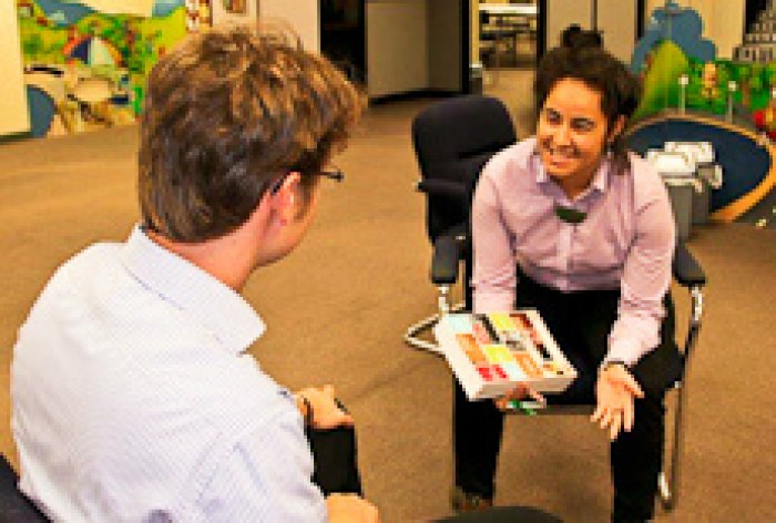 Julia Whaipooti is holding a book talking to a male client in an office