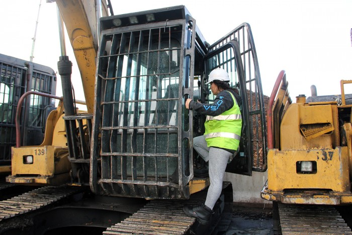 Linda Kingi climbs into the cab of a digger