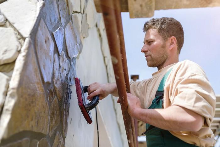 A man sets stone panels into a wall