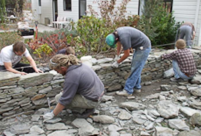 A group of stonemason students helping to build a stone wall