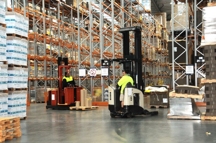 Two storepeople operate forklifts in a warehouse