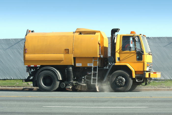 Street/park cleaner operates a yellow streetsweeping truck to clean gutters