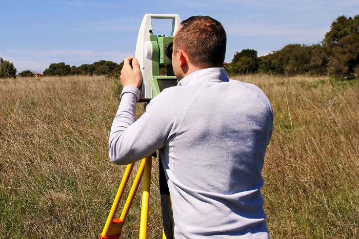 Surveyor using a total station in a field