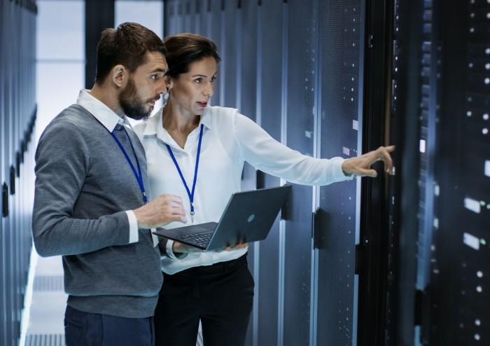 A man holding a laptop talks to a woman who is pointing to a server in a computer server room