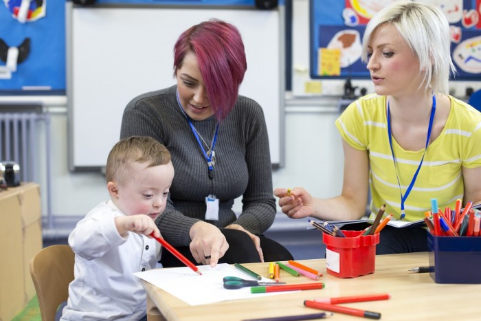 A special education teacher and teacher aide help a toddler learn to hold coloured pencils