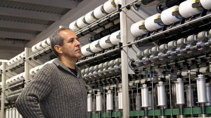 A man inspects a threading machine