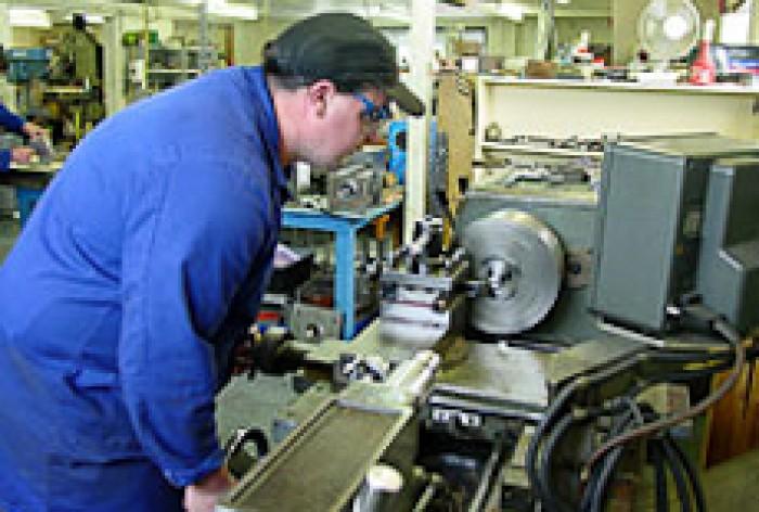A toolmaker watching a machine cutting metal