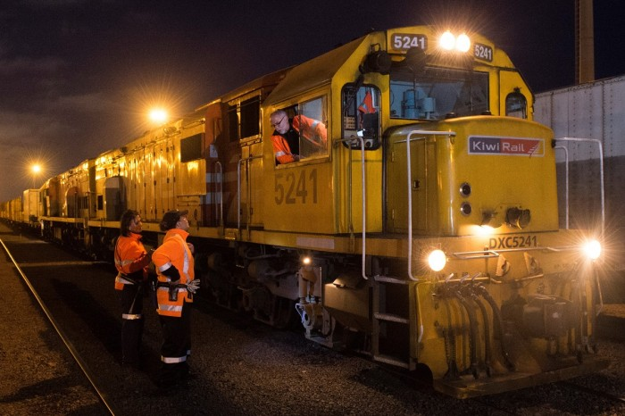 A train driver in a railway yard at night leans out of his cab to talk to two workmates standing below