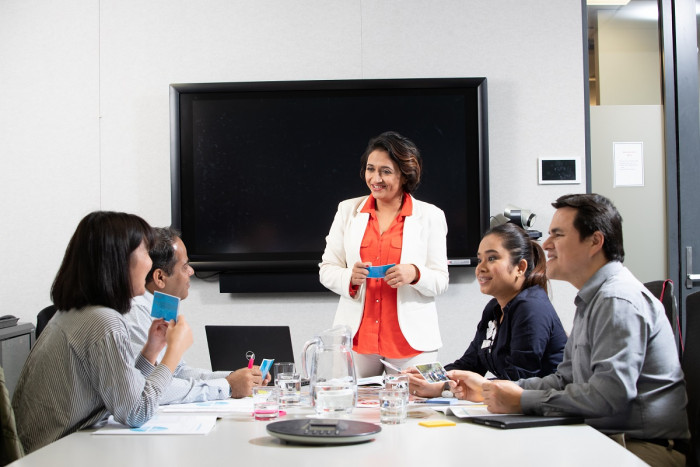 A trainer holds a training session with four other people