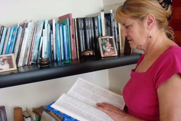 Chantal Taylor-Bizet checking a dictionary as she stands by a bookshelf