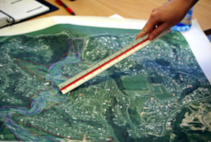 A hand holding a ruler pointing at a map