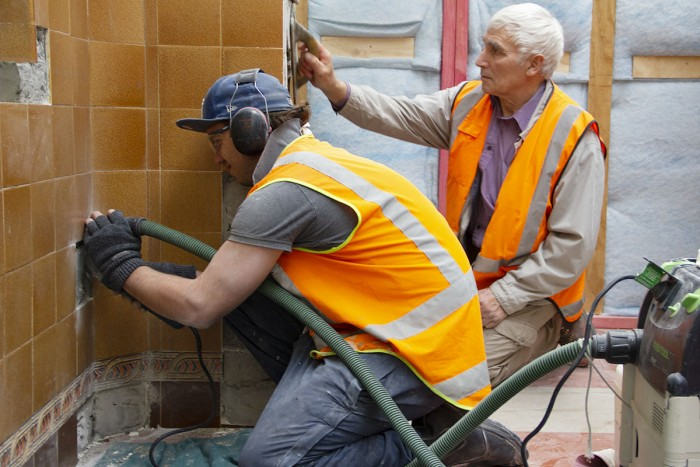 Daniel Van Den Borst uses a tile cutter and dust extractor to repair a tiled wall while a co-worker applies grout in the background