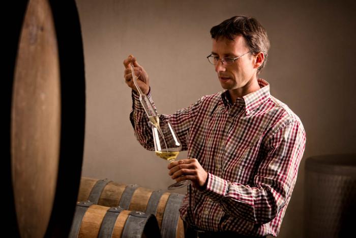 A winemaker sampling wine from a barrel