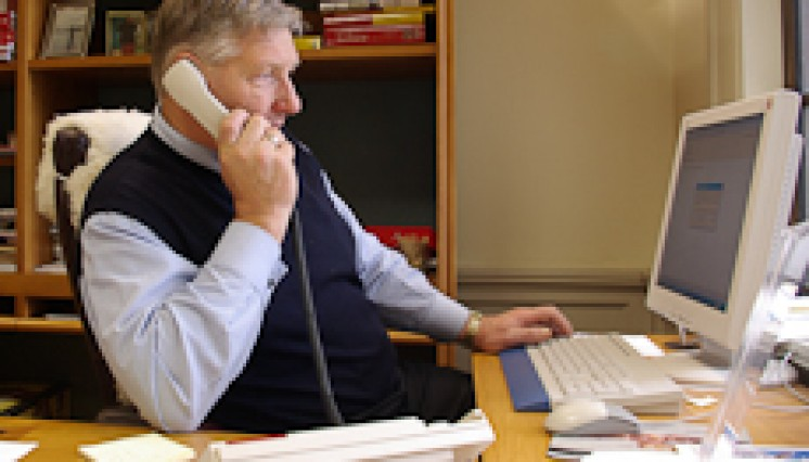 Invercargill MP Eric Roy talking on a telephone at his desk in parliament buildings