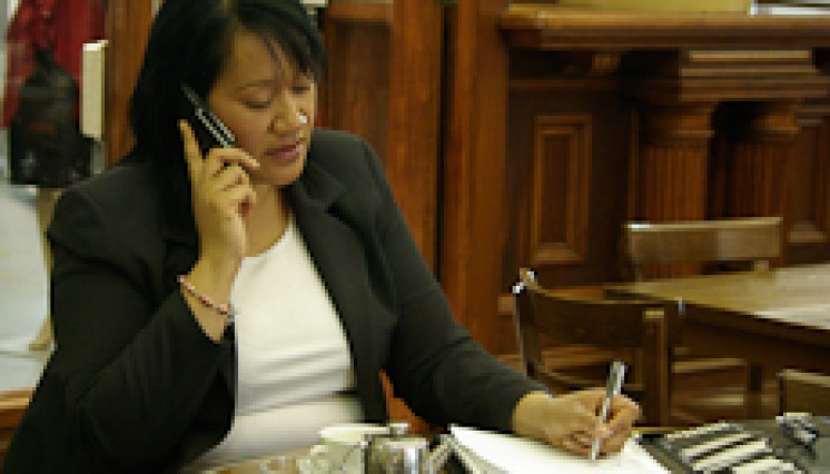 Lina Siu talking on the phone while taking notes
