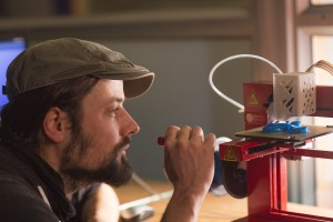 A man observes a 3D printer printing a plastic object.