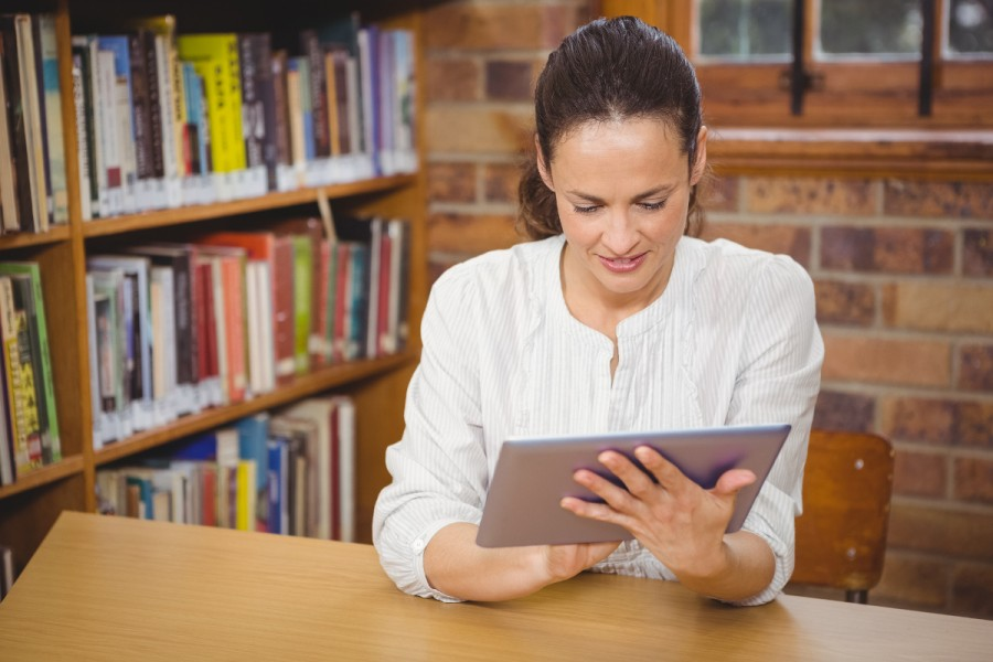 A teacher studies a laptop in a library