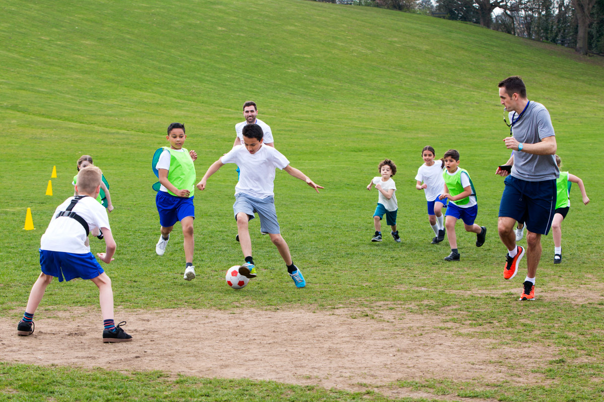 A Group Of Primary School Students Play Football