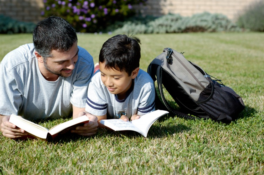 Father and son reading together outside
