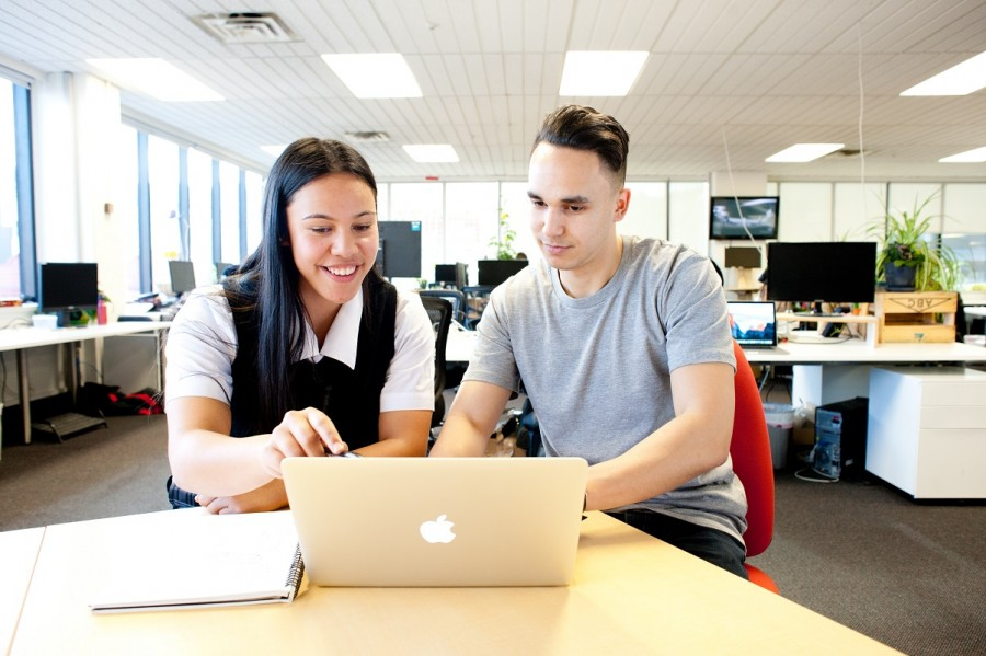 A high school boy and girl sit at a desk and look for jobs on their laptop