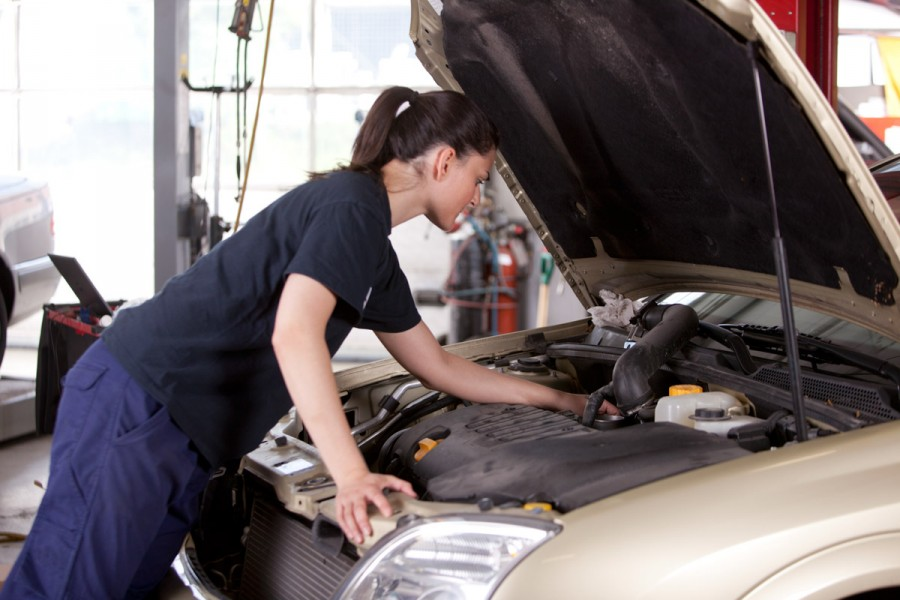 A female student mechanic fixes a car