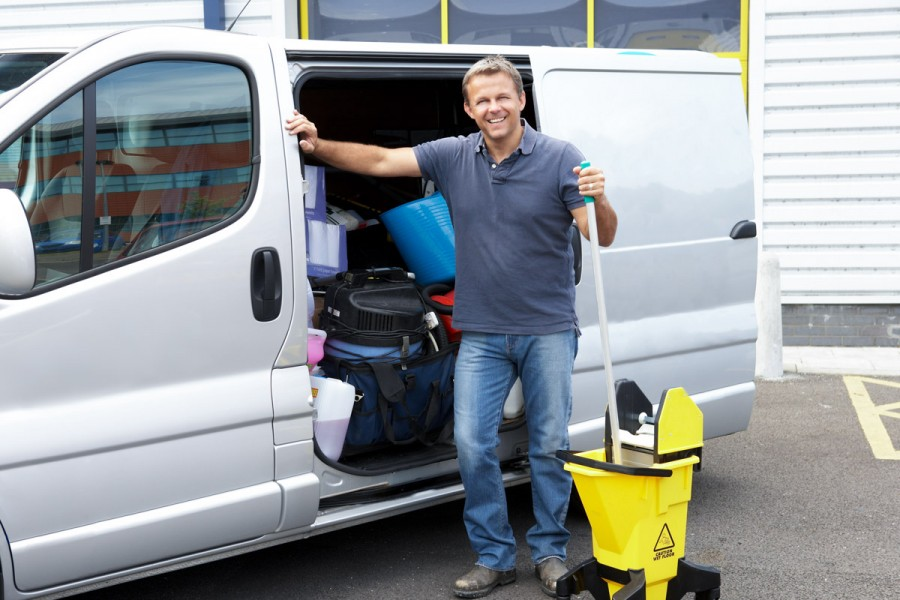 A man stands with a mop by his cleaning van