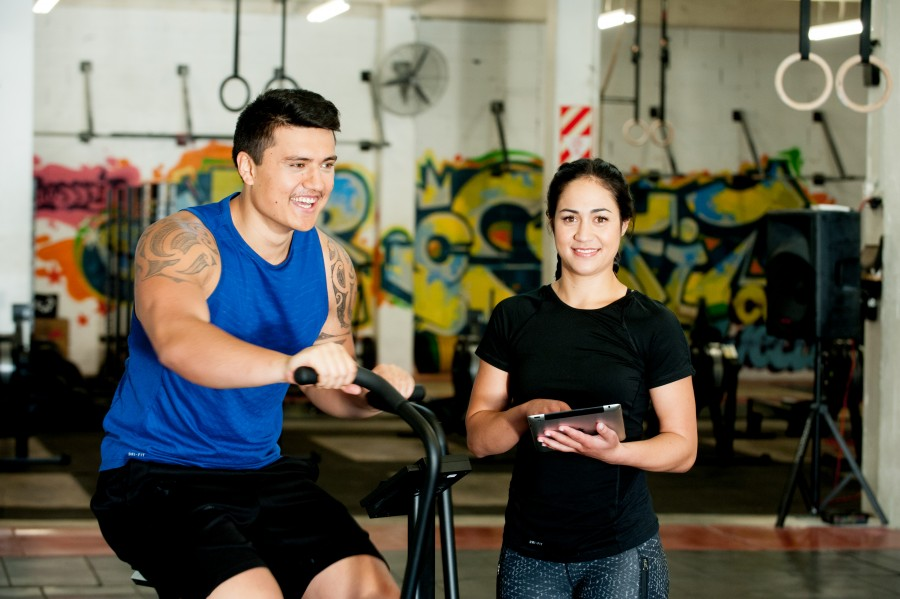 Hero image of a female Maori personal trainer smiling at the camera as a young male client works out on an exercise bike. They are in a gym and graffiti is in the background.