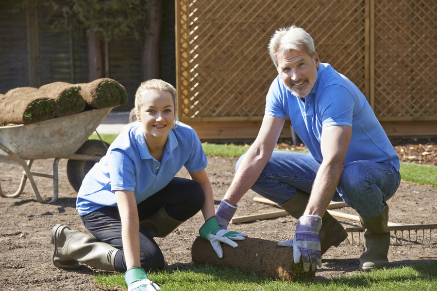 A middle aged man and a young woman smile at the camera as they lay turf on a garden. They are wearing a uniform of denim, and gloves. She is an apprentice. It is sunny.