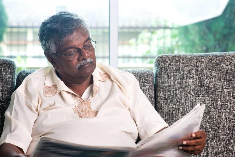 A man reads through a newspaper
