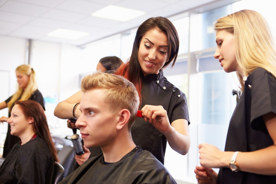 A trainee hairdresser works with a client